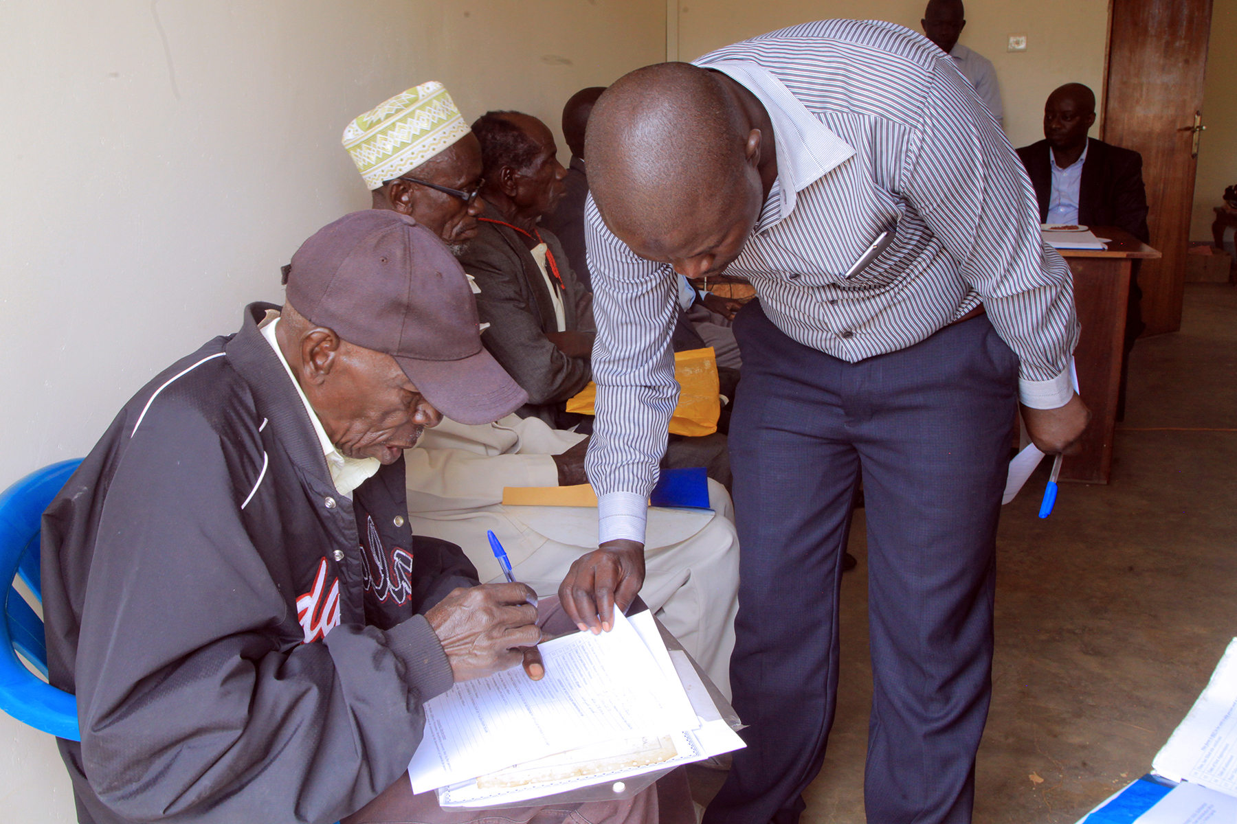 Yumbe district HRO assist pensioners while filling in the required form before validation is done