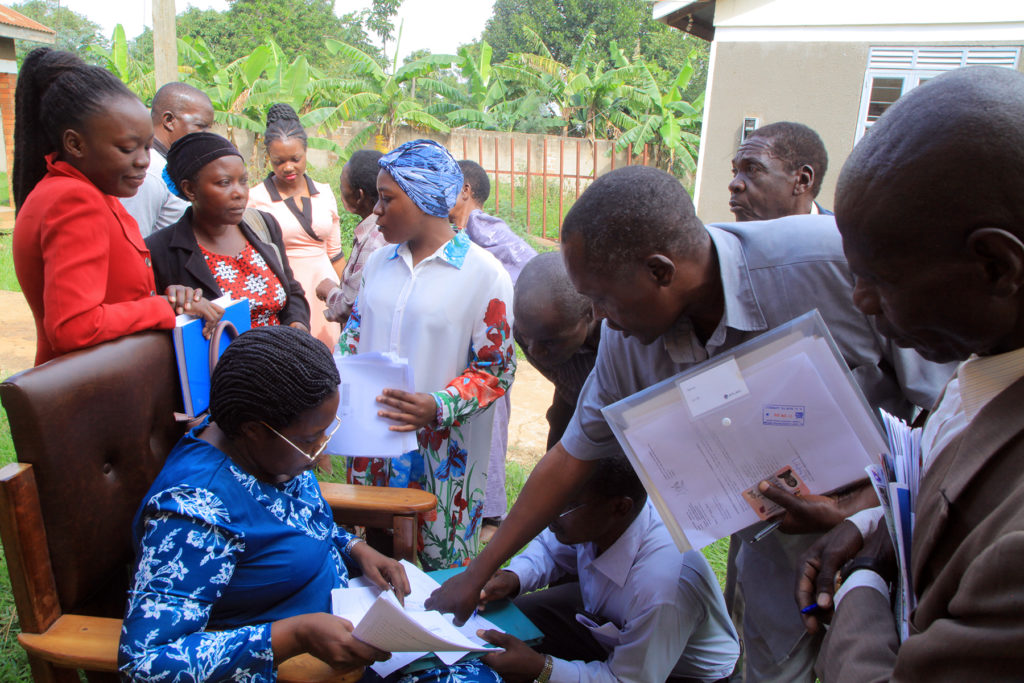 LUWERO DISTRICT PENSIONERS AND CLAIMANTS BEING ASSISTED BY THE TEAM MEMBERS TO FILL IN THE REQUIRED FORMS BEFORE VALIDATION